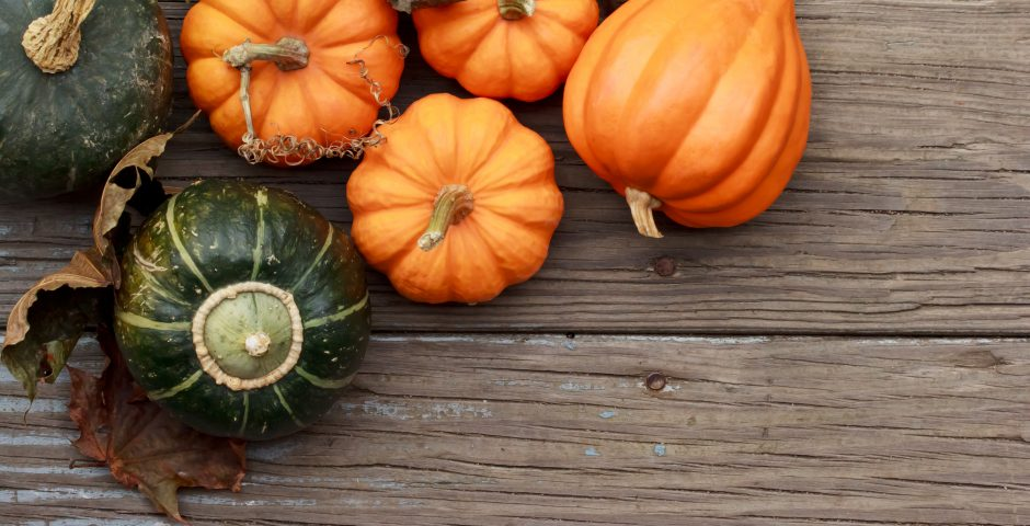 Autumn pumpkins with leaves on wooden board with sqush